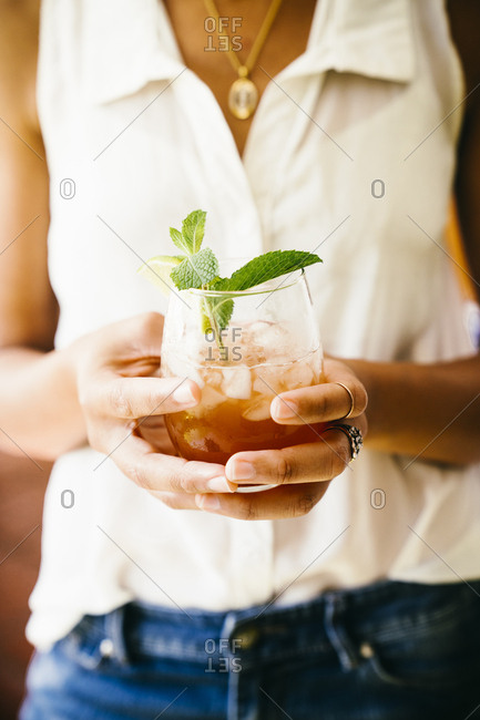 Midsection of woman holding a cocktail  during summer party