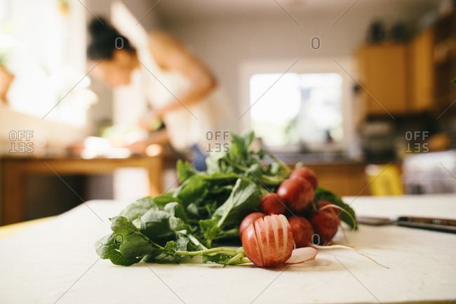 Sliced radish on table with woman cooking in background at home