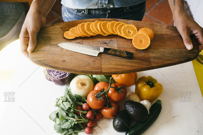 High angle view of woman holding chopping board with sliced orange in kitchen at home