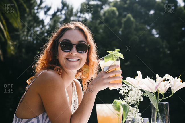 Portrait of smiling young woman wearing sunglasses while holding a cold drink in yard