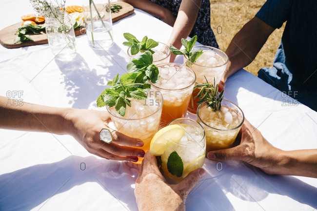 Friends toasting  drinks at table during summer party