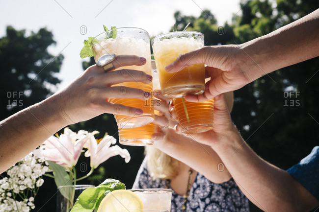Young male and female friends toasting drinks in yard during summer party