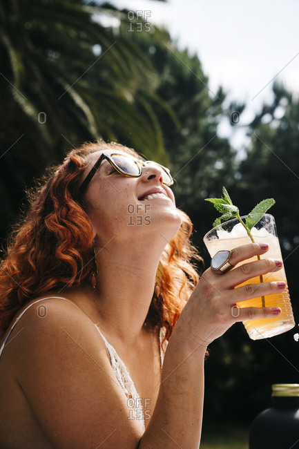 Smiling young woman wearing sunglasses while enjoying cold drink in yard