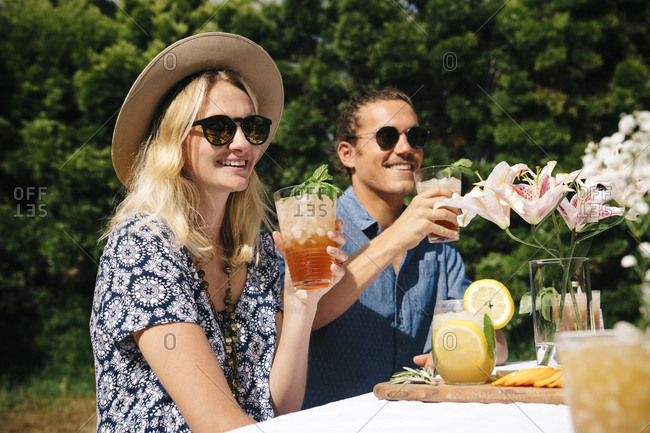 Young woman and man enjoying cold drinks in yard during summer party