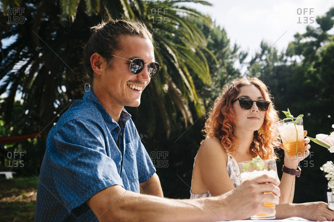 Young man and woman enjoying cold drinks in yard during summer party