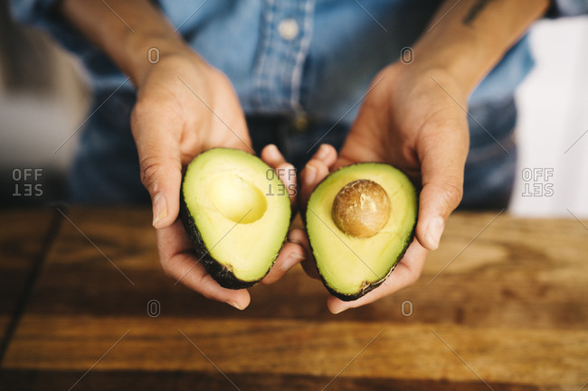 Closeup of young woman holding halves of avocado in kitchen