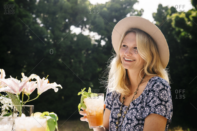 Smiling young woman holding refreshing drink in hand