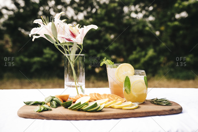 Glasses of drinks with flower vase and fruits slices on chopping board in yard