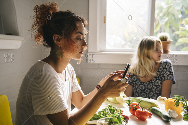 Young woman using mobile phone while preparing food