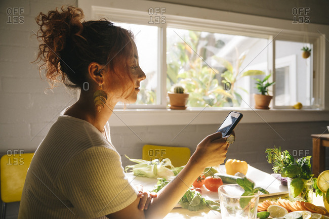 Side view of young woman using mobile phone at dining table
