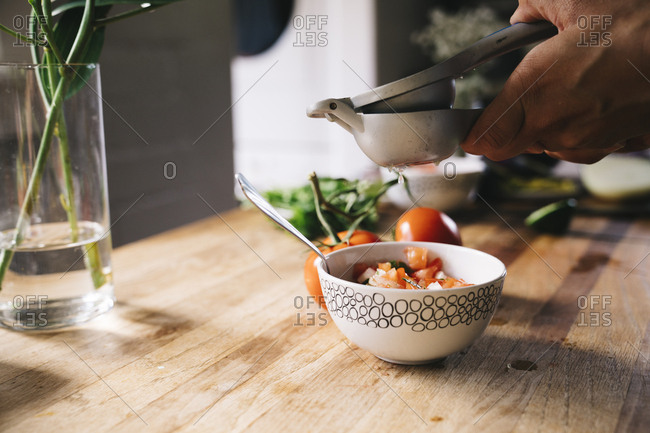 Closeup of woman's hand squeezing lime into salsa in bowl on table at home