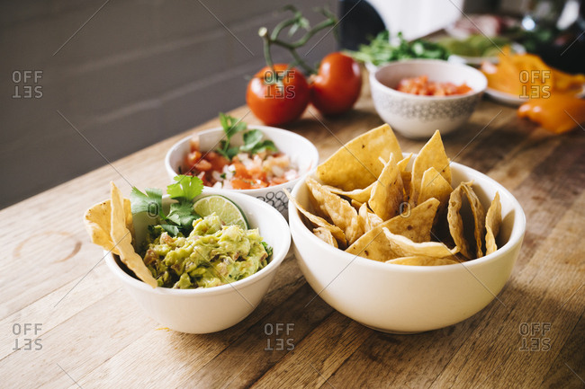 Bowls of tortilla chip with salsa and guacamole dip on wooden table
