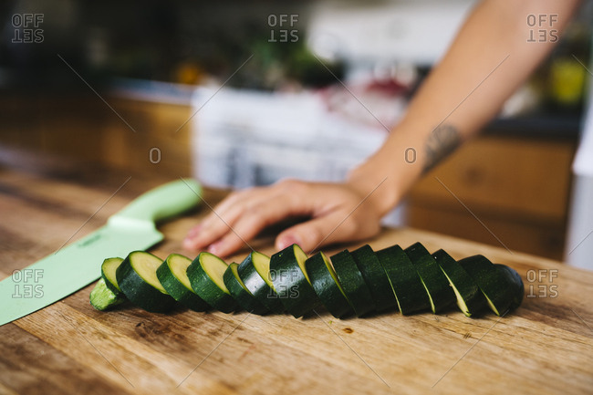 Closeup of sliced zucchini and knife on table in kitchen