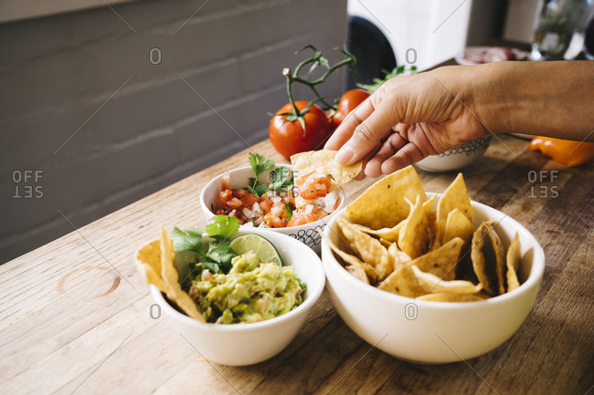 Closeup of hand dipping tortilla chip into bowl of salsa at home