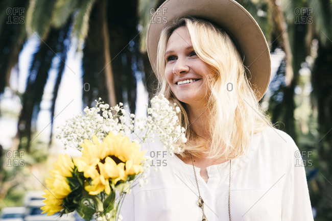 Smiling young woman wearing sunhat while holding flowers in park
