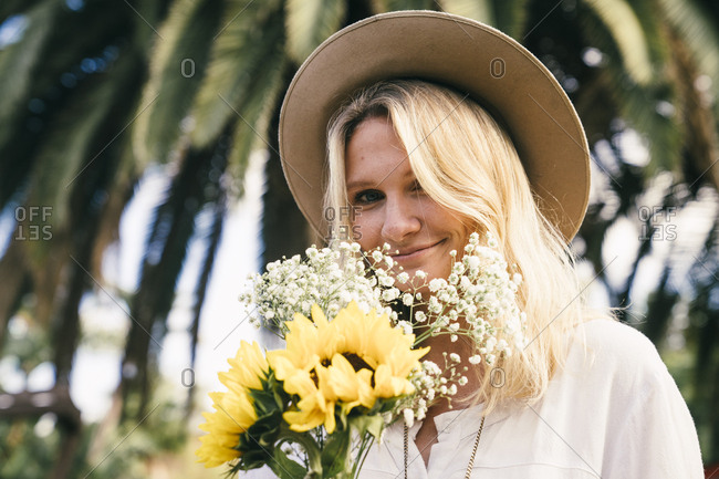 Portrait of beautiful young woman wearing sunhat while holding flowers in park