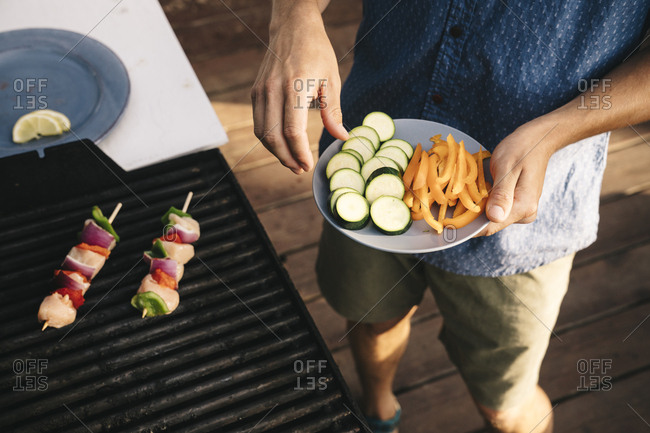 Midsection of young man cooking meat and vegetables on grill