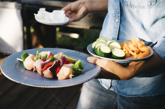 Midsection of woman holding plates with food in yard during party