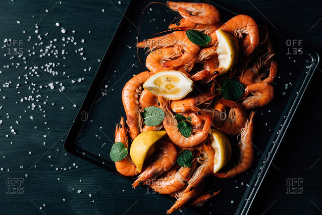 Top view of pile of shrimps with mint and lemon slices on baking tray