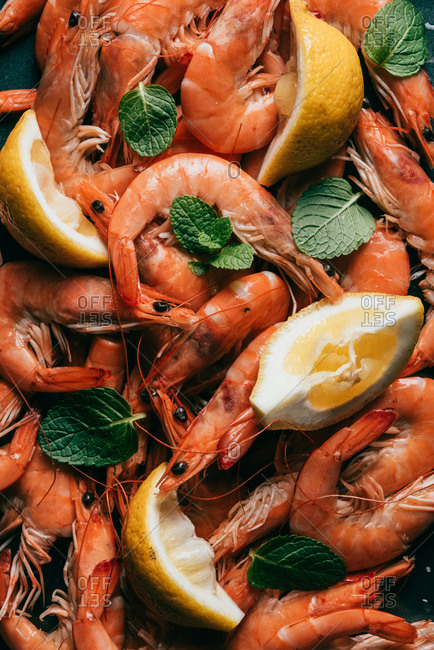 Elevated view of pile of shrimps, lemon slices and mint leaves
