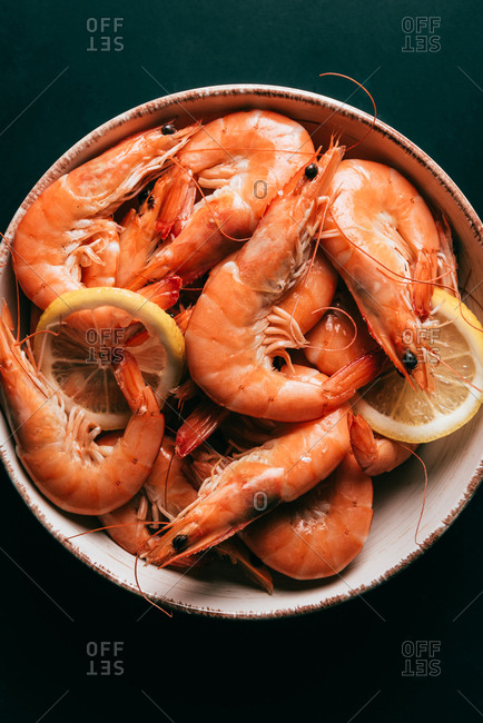 Top view of lemon slices and shrimps on plate