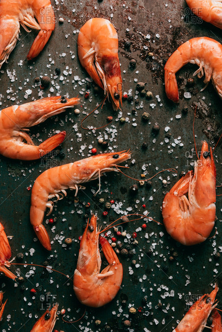 Top view of shrimps on table with black pepper and salt