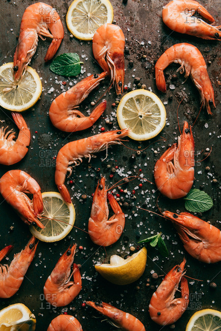 Elevated view of lemon slices, mint leaves and shrimps on table with black pepper and salt