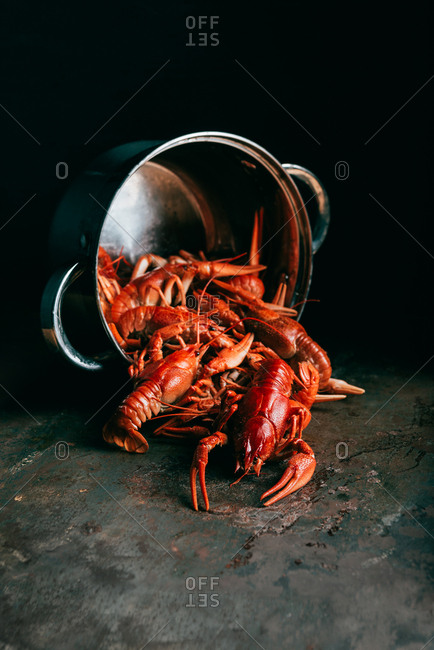 Closeup view of saucepan with pile of crayfishes on rustic tabletop