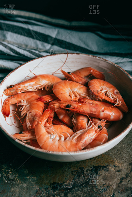 Close up image of shrimps on plate and kitchen towel on table