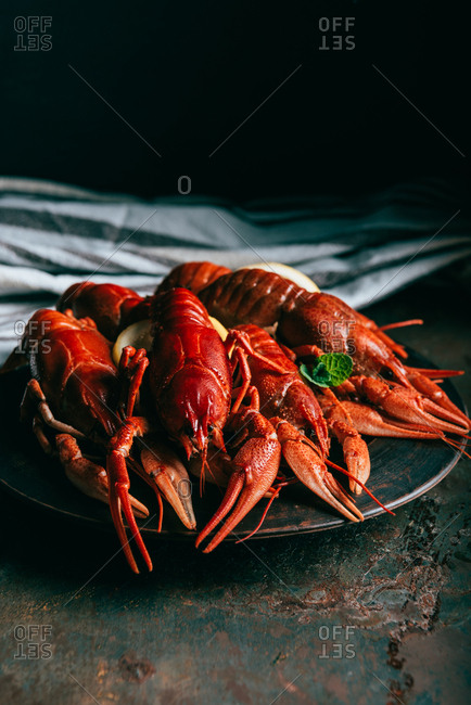 Closeup shot of pile of crayfishes with mint and lemon slices on plate and kitchen towel on table
