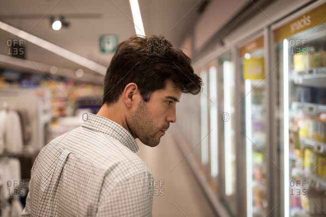 Man standing by refrigerator in supermarket