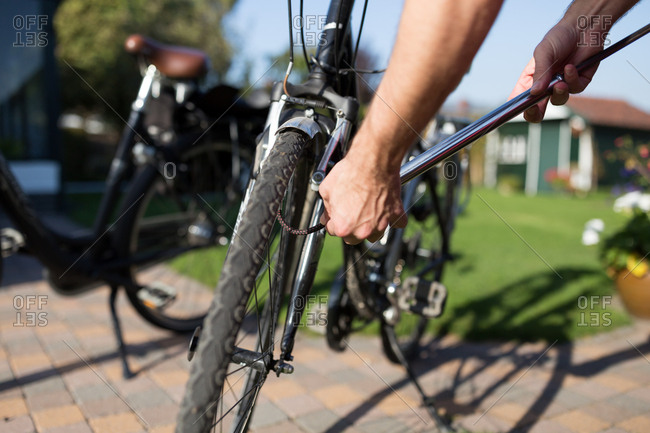 Man pumping up tires of bike