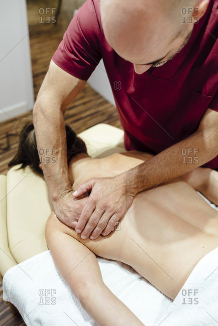 Physiotherapist kneading a client woman's back