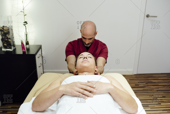 Man physiotherapist massaging a female client neck