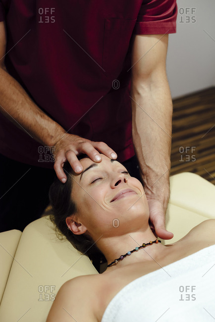Man physiotherapist massaging a female client's head and neck