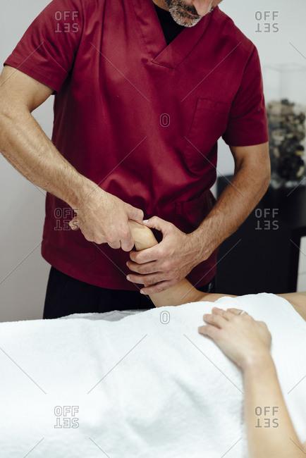 Man physiotherapist massaging a female client's wrist