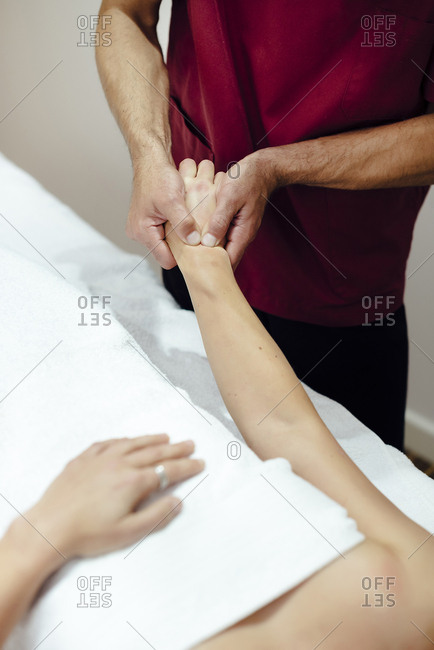 Physiotherapist massaging a female client's wrist