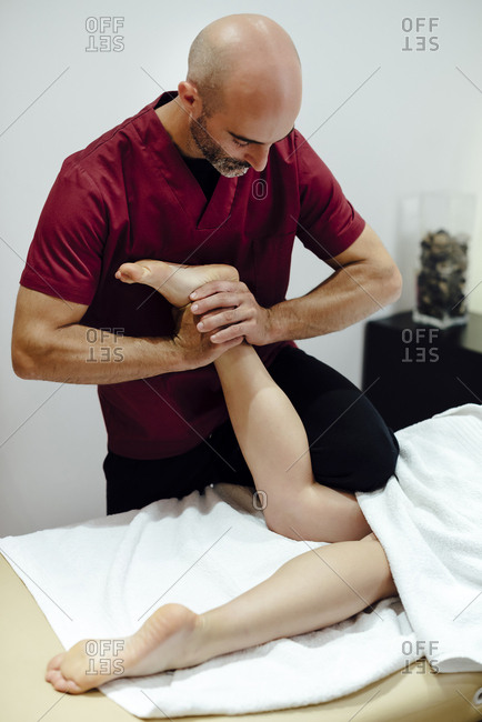 Male physiotherapist massaging a female client's ankle
