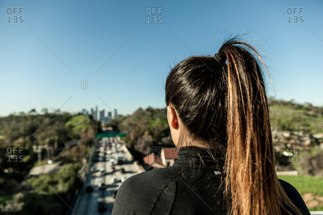 Rear view of woman overlooking highway