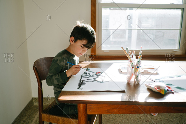Young boy painting at dining room table