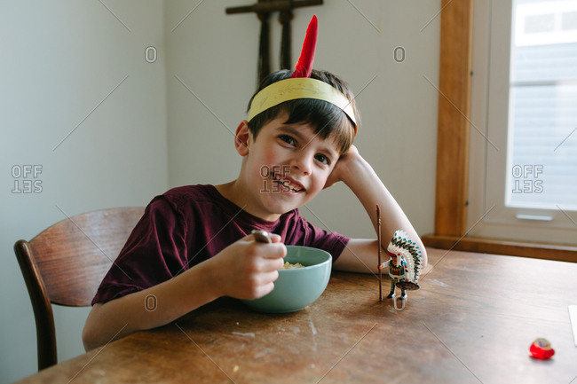 Happy boy playing with indigenous person figurine over breakfast at dining room table