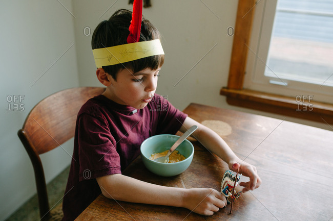 Young boy moving native american figurine toy around wooden table at breakfast