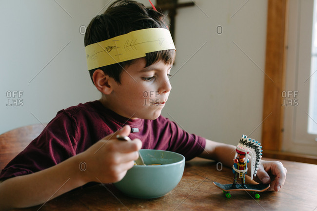 Hungry boy pushing native american toy on skateboard at breakfast table