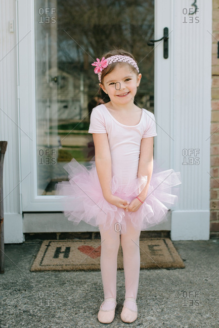 Young girl posing on porch in ballet costume