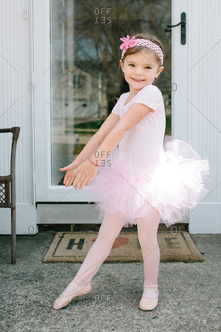 Little ballerina doing a dance pose outside house