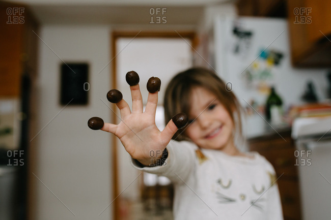 Little girl showing off olives on tips of fingers