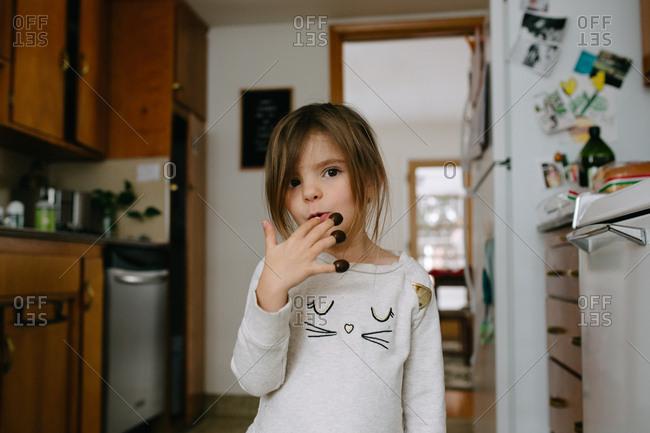Brunette preschooler eating olives off her fingertips in kitchen