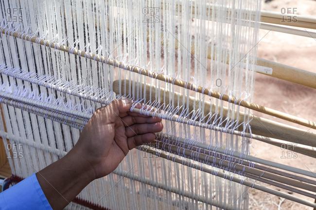 Ganado, Arizona - April 26, 2018: Hand view of native person using loom at Hubbel Trading Post