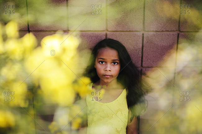 Portrait of serious little girl through tree branches