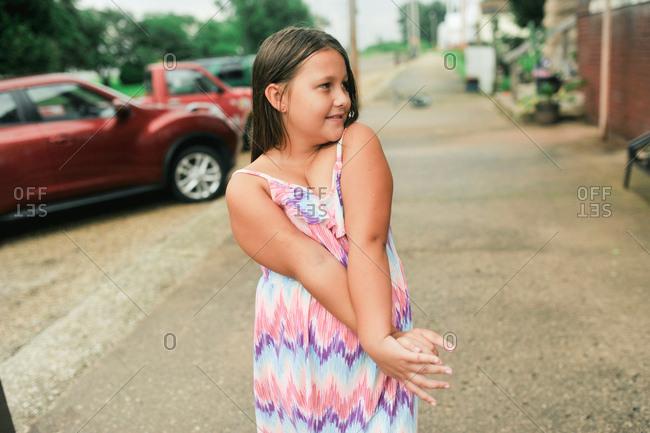 Portrait of a girl wearing a sundress standing on the sidewalk